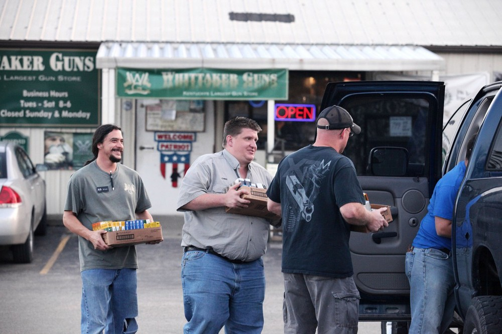 Brian Greenwell (left) and Chris Whittaker help a customer carry ammo to his truck.