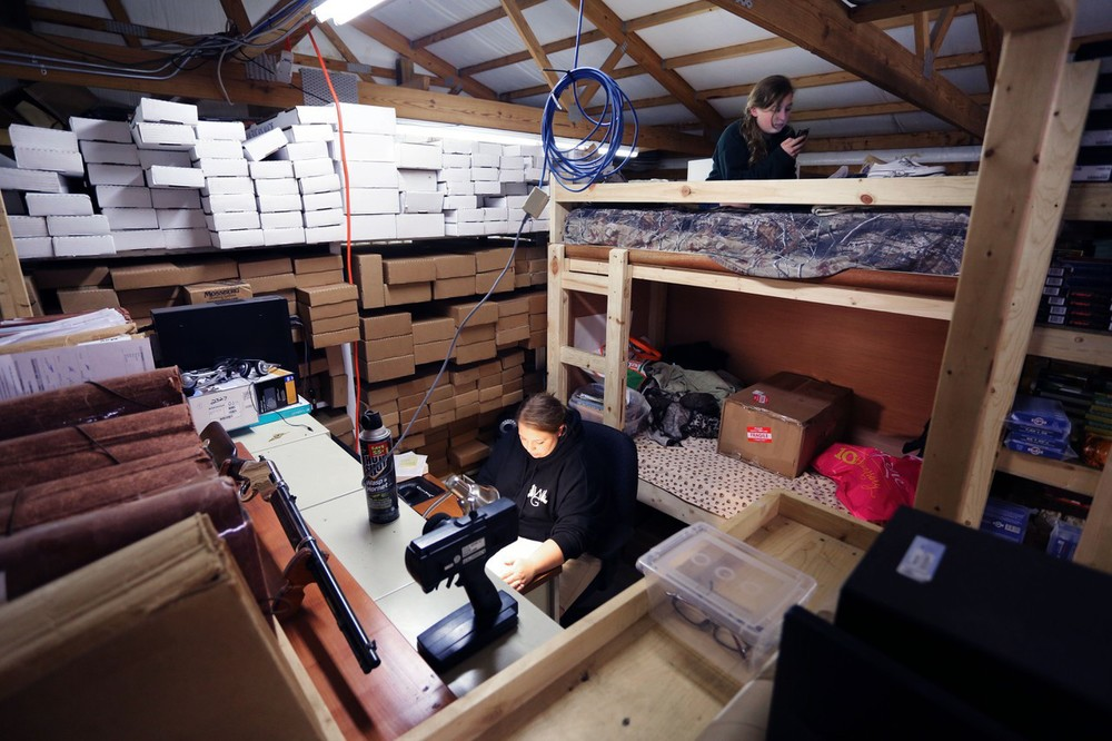 Shelby Fulkerson, 12, texts atop a bunk bed as Chandra Burcham works on paperwork in the overstock room of the Whittaker Guns in West Louisville. Shelby and her brother Cooper, 8, have nearly grown up in the store. Their mother, Cindy, had a small crib behind the counter when she was a child.