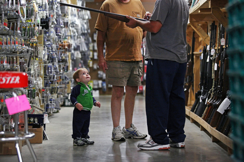 Carter Johnson, 16 months, takes aim at a rifle examined by his dad and granddad at Whittaker Guns in Owensboro, Ky, on Wednesday, October 15, 2013.