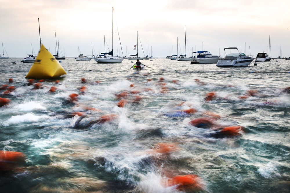Swimmers rush pass the starting line of the Chicago Triathlon in Monroe Harbor on Sunday, August 24, 2014.