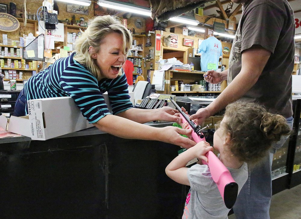 Cindy Fulkerson hands Kylie Hardin a .22 Cricket pink rifle at Whittaker Guns in West Louisville. Her father, John Hardin, bought the gun for Kylie's 4th birthday. John received his first gun when he turned 6.