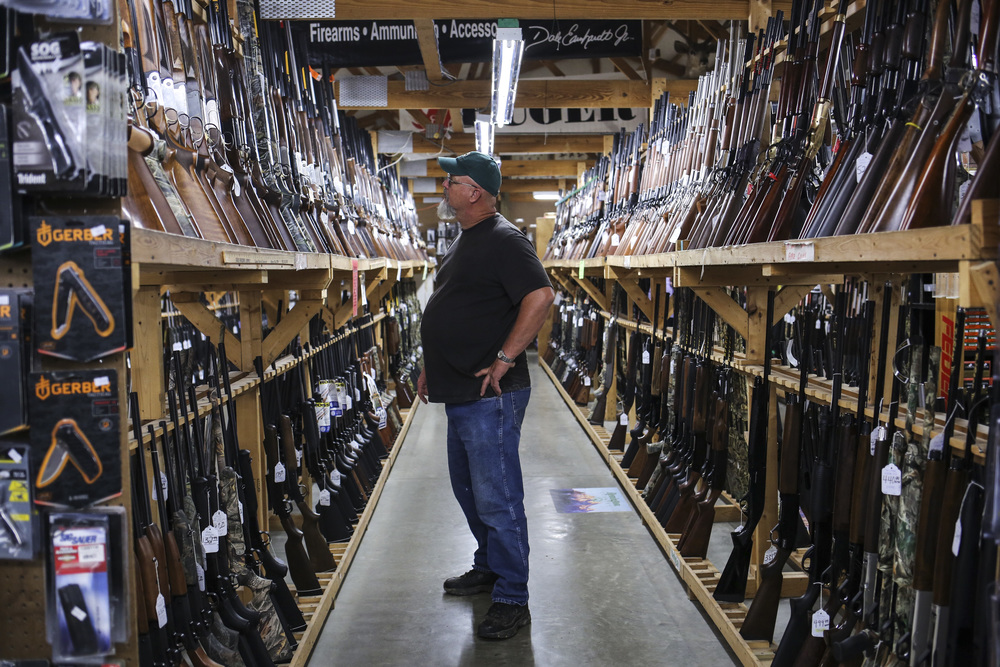 A customer considers the display rifles at Whittaker Guns in West Louisville. The store boasts a selection of 8,000+ guns.