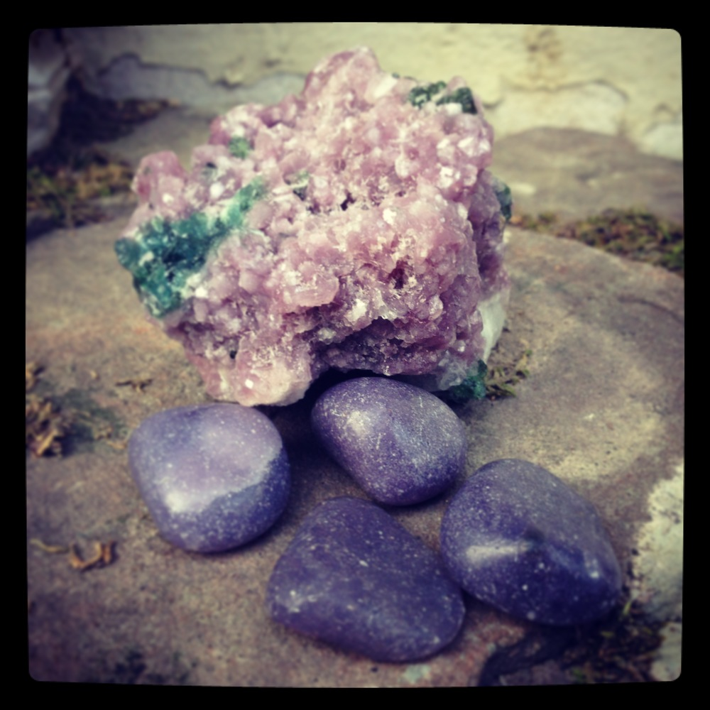 The large stone is Lilac Lepidolite with Green Tourmaline in matrix, the tumblies are Lepidolite. It ranges in color from purple to pink to lavender, though it can be almost clear or grey.