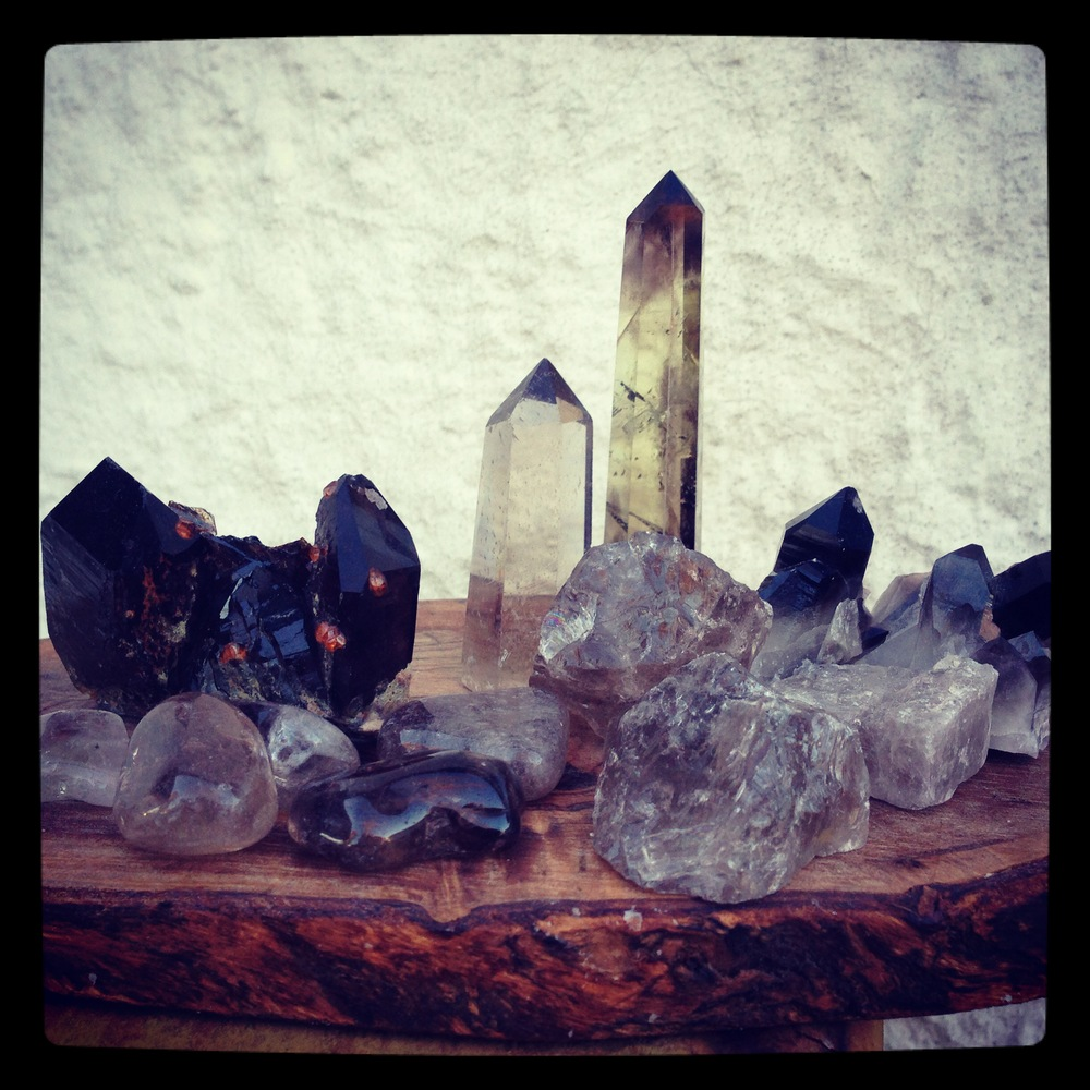 Smoky Quartz ranges in color from light grey to nearly black with brown in between. This picture shows two Smoky Quartz obelisks, a Smoky Quartz cluster, raw Smoky Quartz, Polished Tumblies, and the Smoky Quartz with Spessartine Garnet.