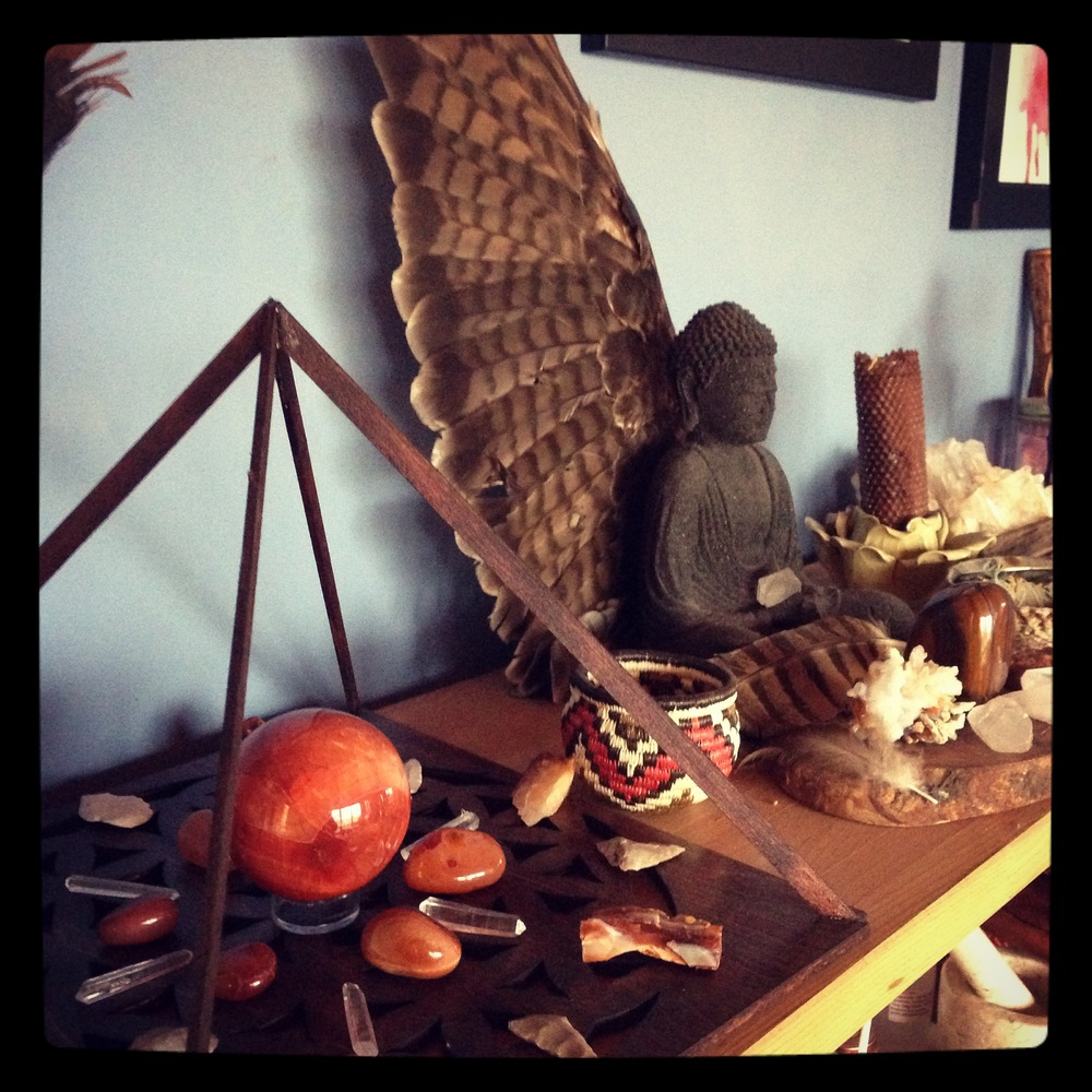 My current altar features a creativity grid with Carnelian and Clear Quartz. A Red Tail Hawk wing sits behind my Buddha with some owl feathers, a Tiger Iron chunk, two Fire Agates,and some clear quartz.