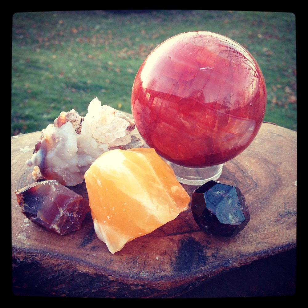 From 12 O'clock, Carnelian sphere, Garnet, Orange Calcite, raw Carnelian, and Fire Agate.