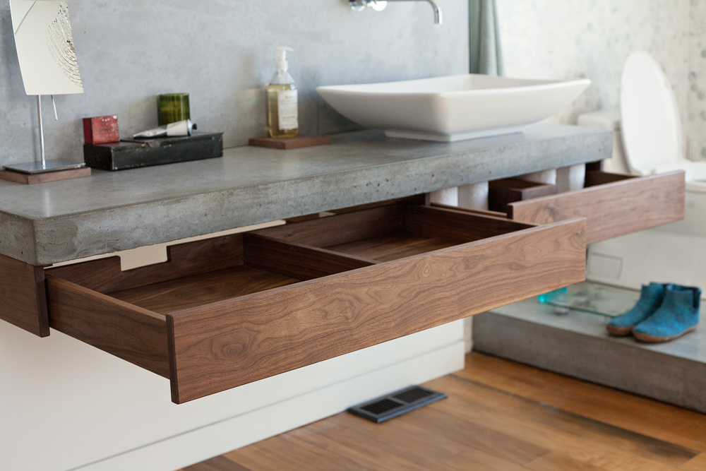 Walnut sliding drawers were added under the polished concrete counter for more storage options.