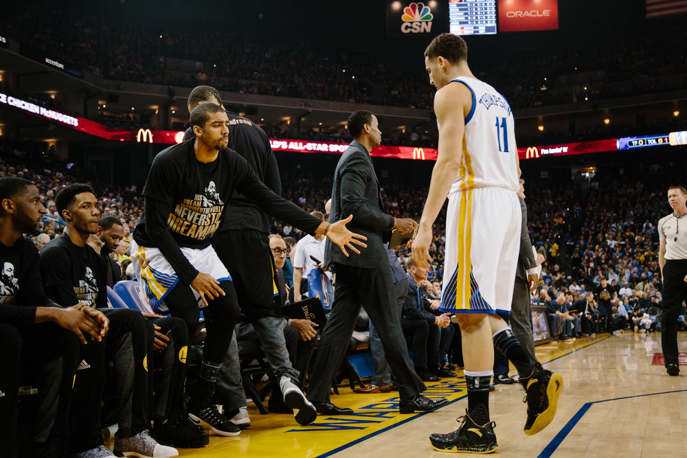 McAdoo watches the Warriors home game against the Cleveland Cavaliers from the bench, high-fiving his teammate Klay Thompson.