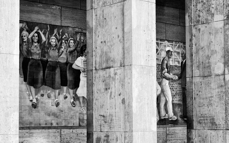CULTURAL REALISM   A mural of happy communists graces the side of the current home of the Federal Ministry of Finance in the former East Berlin. The building was built in 1935 as the Reich Ministry of Aviation. During the Cold War it became home to the House of Ministries. The House of Ministries was also part of the demonstrations that took place in June 1953, when the protesters gathered there to demand social reforms and free elections. Hundreds of demonstrators were killed and thousands more were jailed. Several Soviet soldiers were reported to have been executed for their refusal to shoot unarmed demonstrators. Today a monument in front of the ministry commemorates the June uprising.