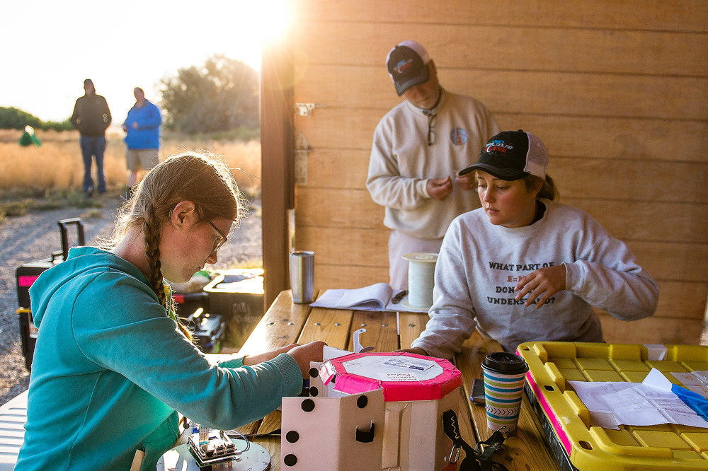 As the sun rises over the MSU team's launch site, team members Katherine Lee, left, and Darci Collins prepare a camera system they designed to capture images of the sun's atmosphere during the eclipse.