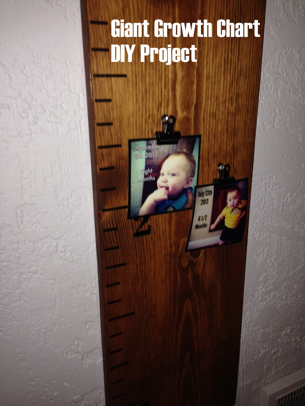 A photo of my finished giant growth chart DIY project complete with some photos of Mateo pasted on it.