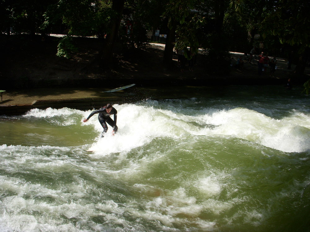 "A photo of a guy surfing at Englisher Garten. The Englischer Garten, German for ""English Garden"", is a large public park in the centre of Munich, Germany, stretching from the city centre to the northeastern city limits."