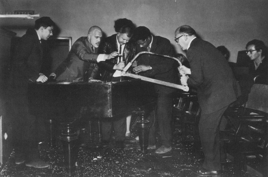 "George Maciunas, Dick Higgins, Wolf Vostell, Benjamin Patterson & Emmett Williams performing ""Philip Corner's Piano Activities"" at ""Fluxus Internationale Festspiele Neuester Musik,"" Weisbaden (1962). Photograph by Hartmut Rekort."