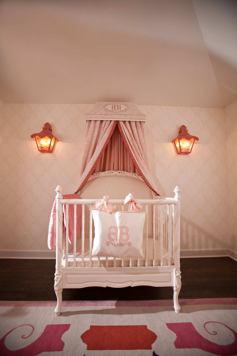 The focal point of any nursery is the baby in it. That's why we created this bespoke corniceover the crib, flanked by custom coral pagoda sconces.