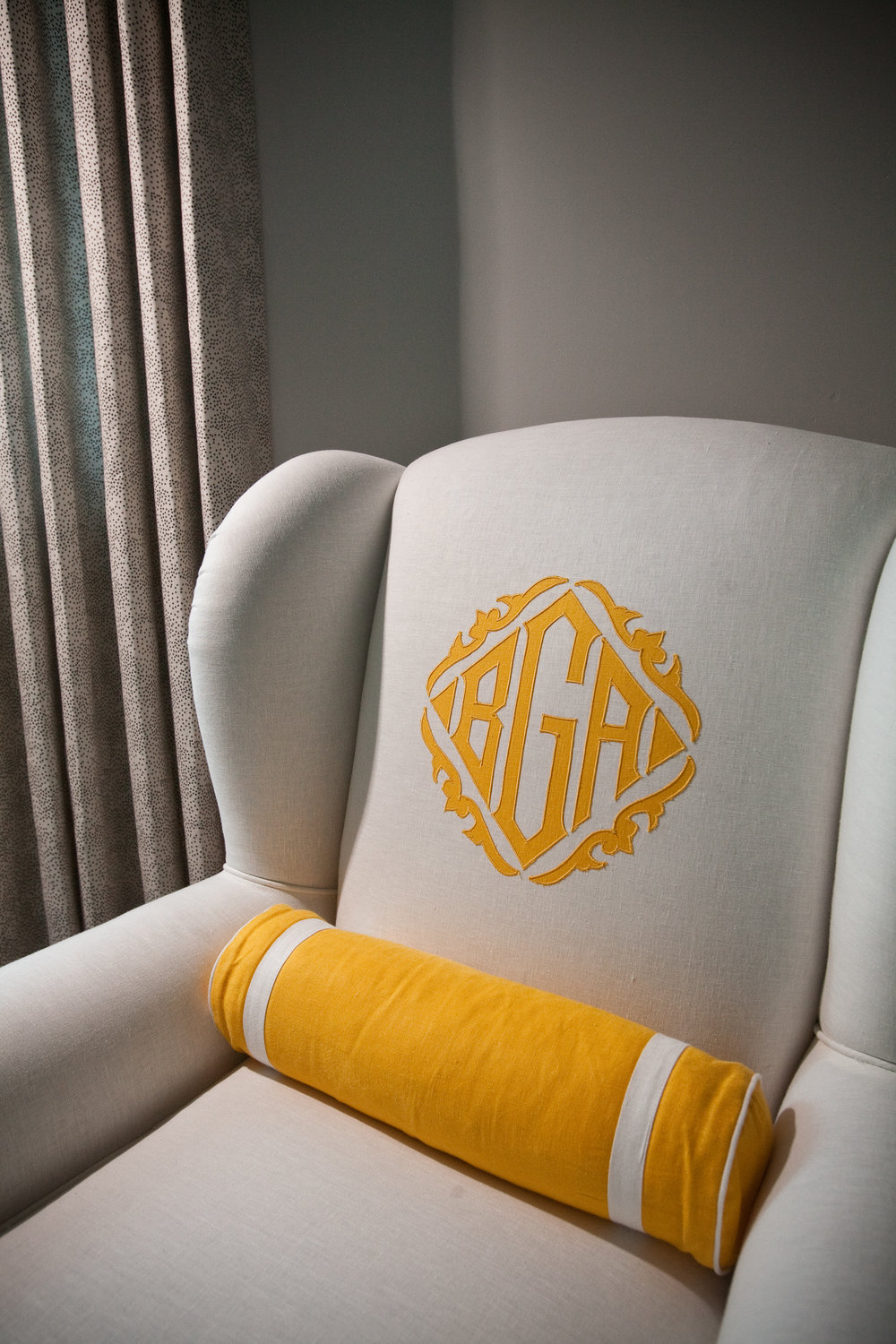 This cheerful bespoke monogram was created especially for this comfy guest room readingchair to unify with the custom Leontine Linens beddings.