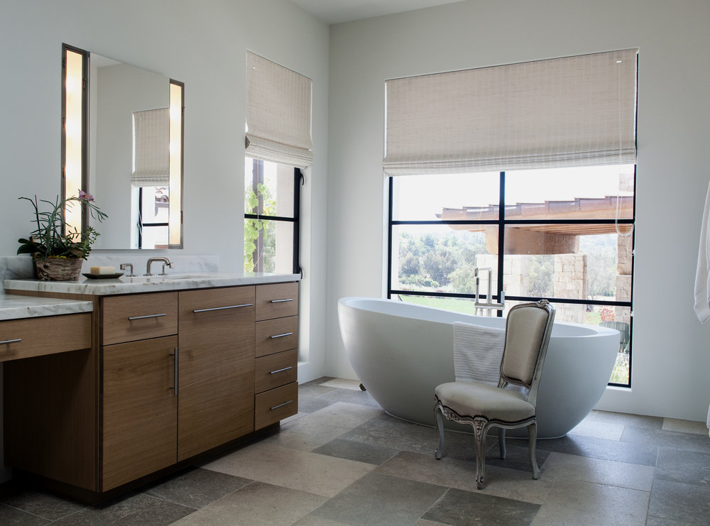 A modern Waterworks tub happily coexists with a charming antique chair, enjoying view to theguest house and the hills and orchards of Rancho Santa Fe.
