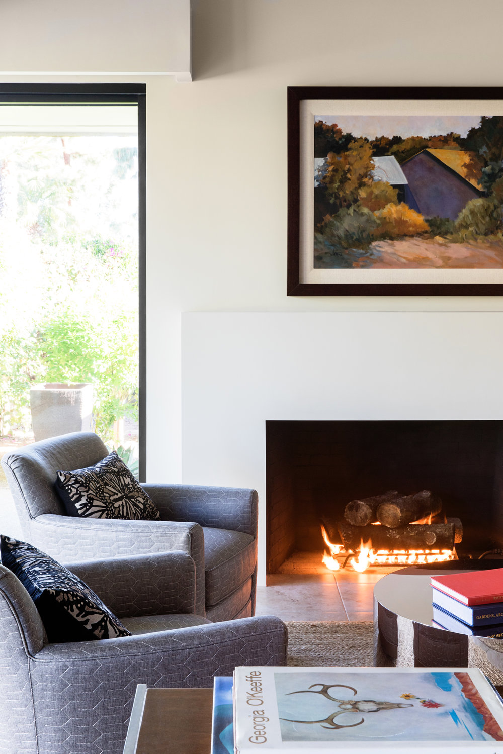 Above the modern fireplace, a painting by Sheryl Derrick, a personal friend of the homeowners, recalls warm memories in the mountains of New Mexico.