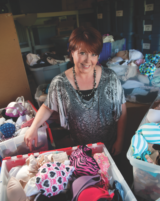 Co-founder, Kimbra Langas stands surrounded by donated bras.