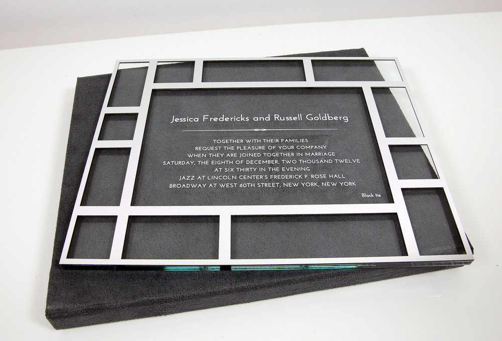 An acrylic glass wedding invitation with silver chrome overlay. The invitation is encased in a microsuede invitation box with magnetic closure.