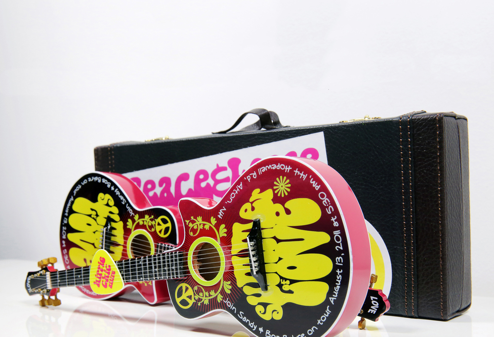 "A 60s themed ""Summer of Love"" party invitation. Custom hand painted mini guitars sent in guitar cases adorned with bumper stickers for a hippie vibe."