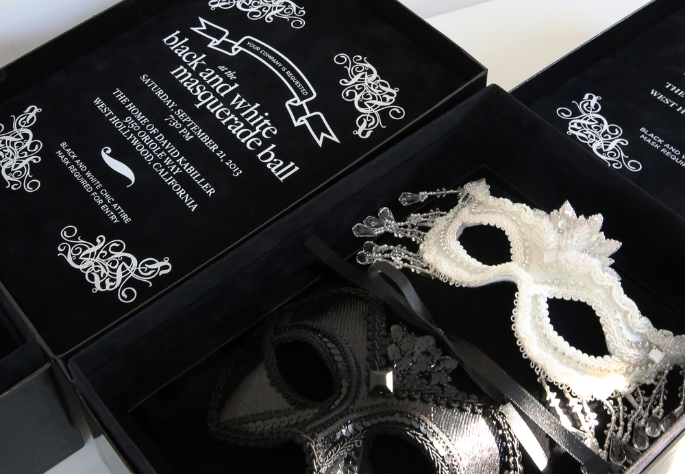 An invitation to a black and white masquerade party. His and hers custom-designed, jewel and sequin masks tied to a black velvet pillow. The invitation box featured a black velvet interior and white foil printing.