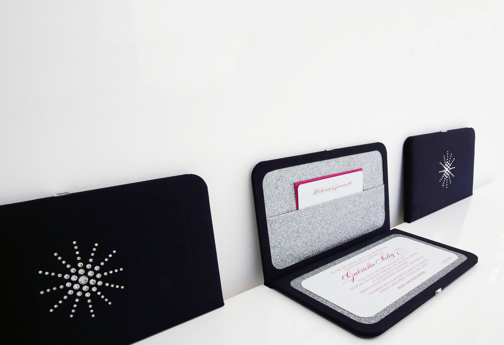 A silk invitation clutch for a glamorous winter-themed Bat Mitzvah. Adorned with a Swarovski crystal snowflake and closure. Opens to reveal a silver glitter interior.