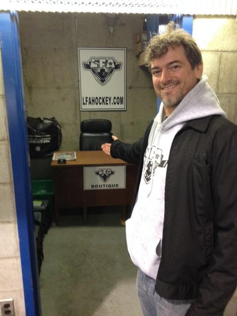 Le prez de la ligue montre fièrement son nouveau bureau à l'aréna (photo par Larry)