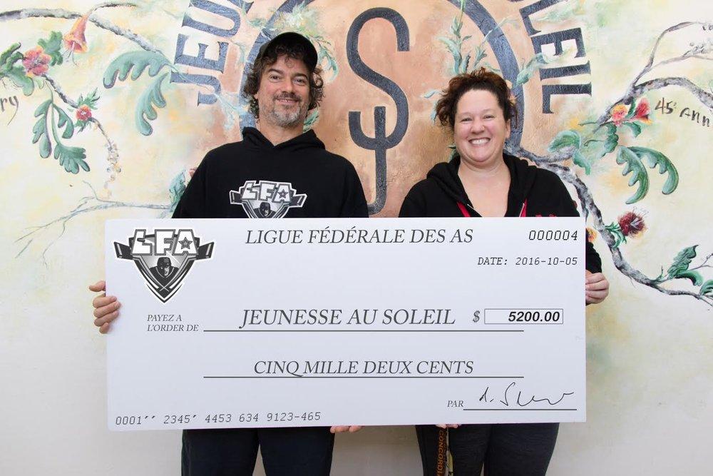 Jean-François DesBois, PDG de la LFA, remettant un chèque de 5200$ à Kara De La Peralle de Jeunesse au Soleil. Les fonds ont été recueillis lors du Match de Championnat estival 2016 et serviront à financer le programme de développement hockey SLAP de la fondation.