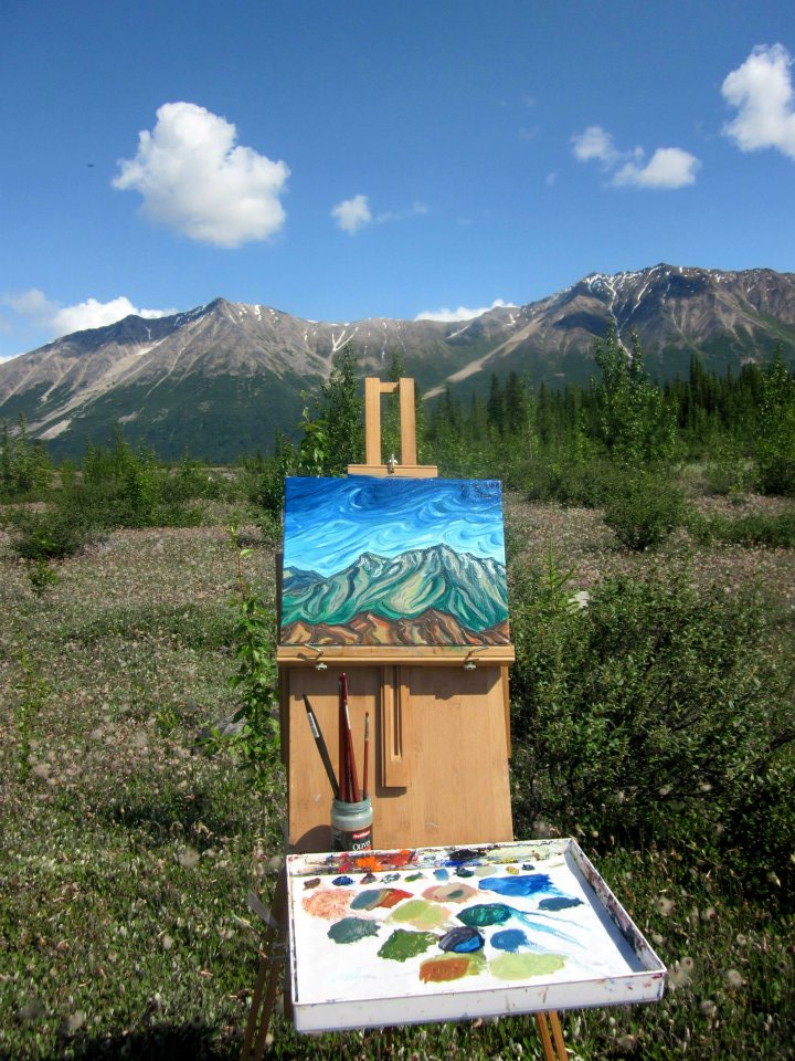 A painter sets up an easel to study the landscape
