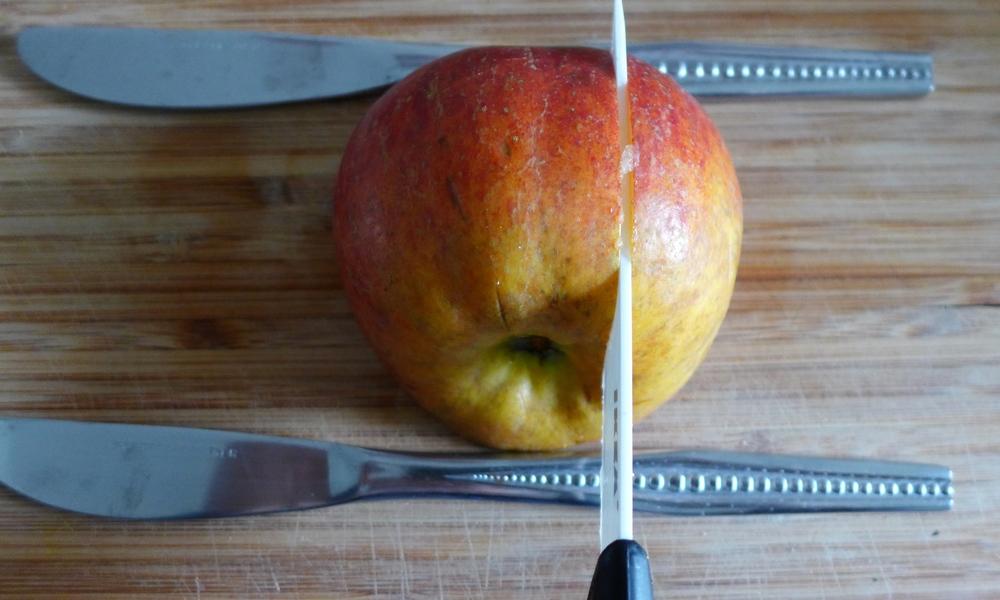 Apfel mit Strunk nach unten zwischen zwei gleiche Messer legen und wie am Foto vertikal und anschließend horizontal einschneiden. Die Messer verhindern das komplette durchschneiden des Apfels.