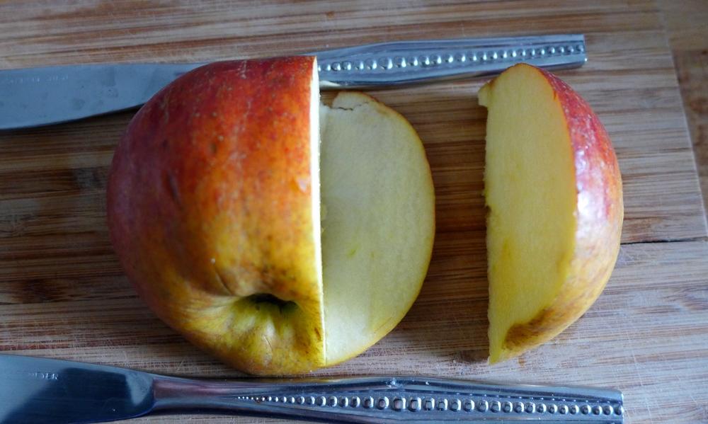Das ausgeschnittene Apfelstück beiseite legen und noch einmal mit Hilfe der Messer vertikal und horizontal einschneiden und ein erneutes kleineres Stück rausschneiden.
