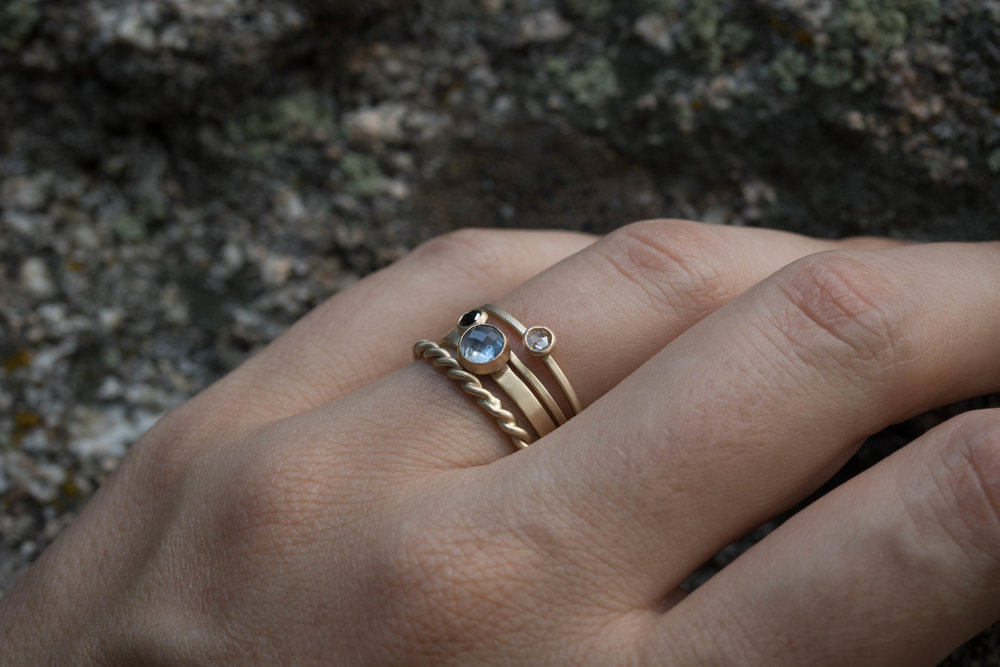 The Plain Rope,  Katherine Sapphire ,  Black Diamond Terence  and  White Diamond Terence  rings all in 14k yellow gold.