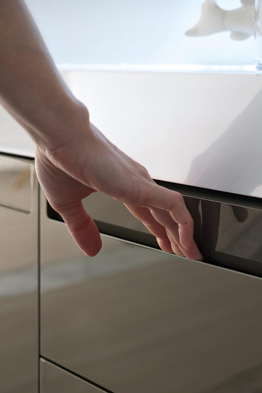 Maniglia a scomparsa - La superficie continua dell'anta si fonde con la maniglia, un elemento a scomparsa in grado di mimetizzarsi completamente o al contrario di emergere in base al colore applicato.