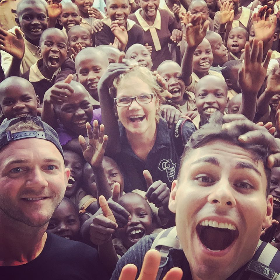 Nathan with his mom, friend Lloyd and the students at the first school his foundation built in Kenya.