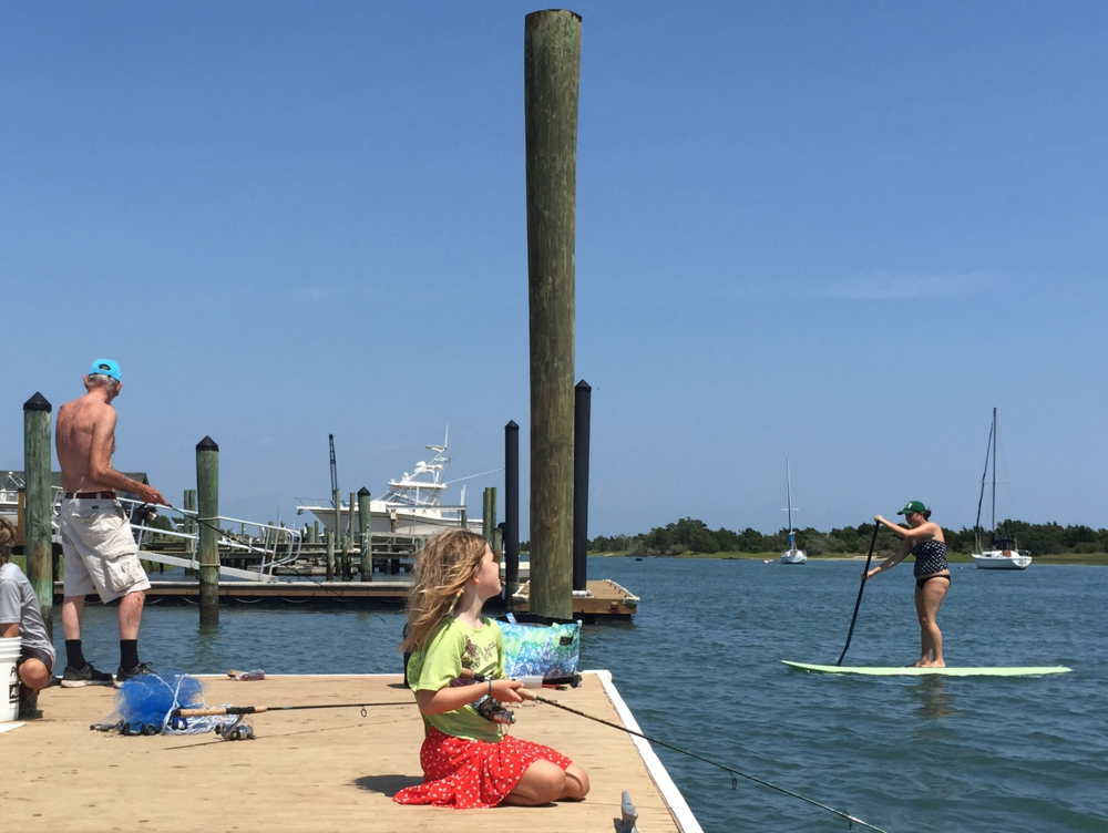 We have often referred to Beaufort's waterfront as BusyTown.  This picture seems to capture the summer hustle well.  Seven year old Liza Taylor fishes in the foreground while surrounded by all sorts other forms of fun.