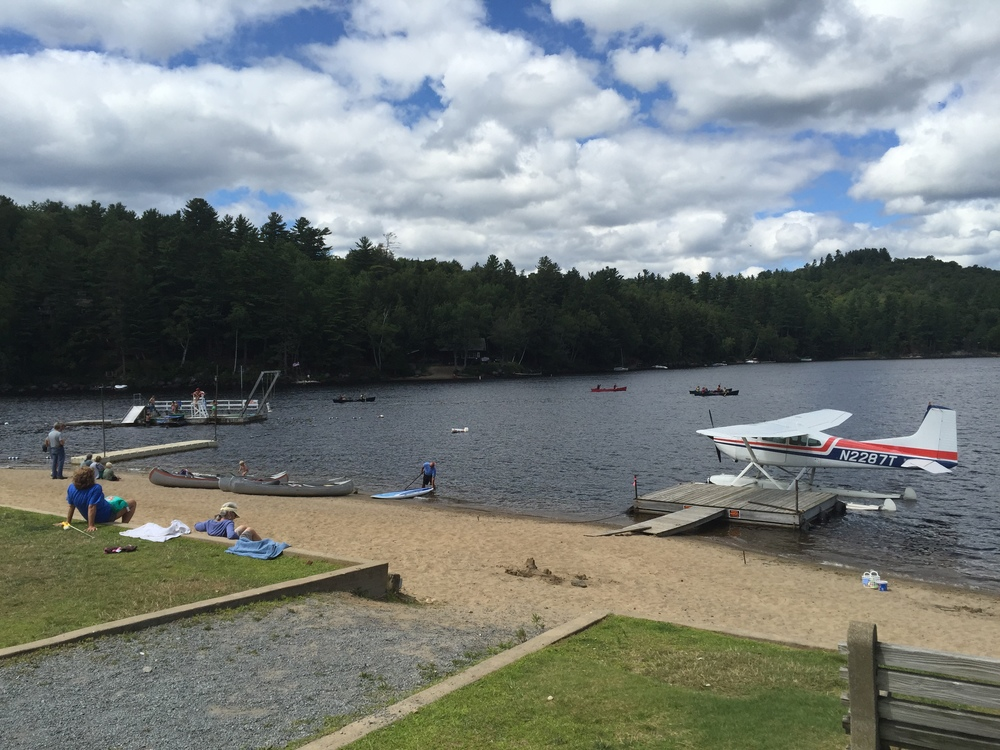 Bi-plane, canoes and town dock on the beach at Long Lake, New York