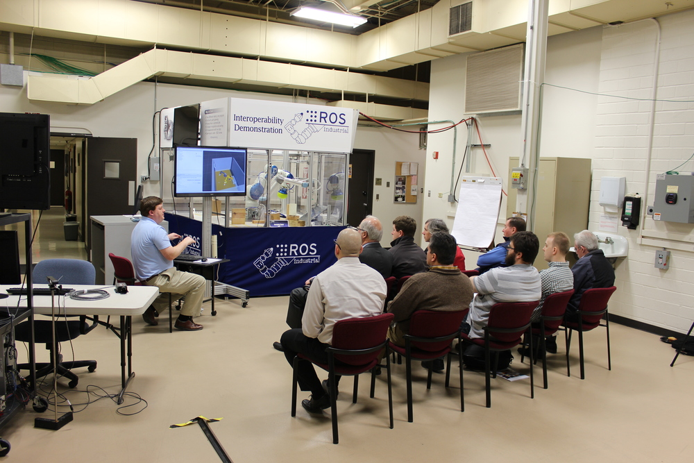 March: Showing the demonstration collision-free pick and place system during a lab breakout session.