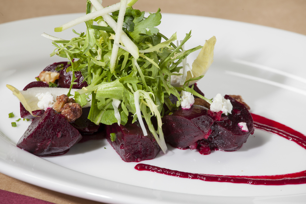Herb roasted beets with frisée, goat cheese and candied walnuts.