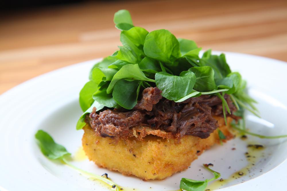 polenta crocante com rabo de toro desfiado e minibroto de agrião