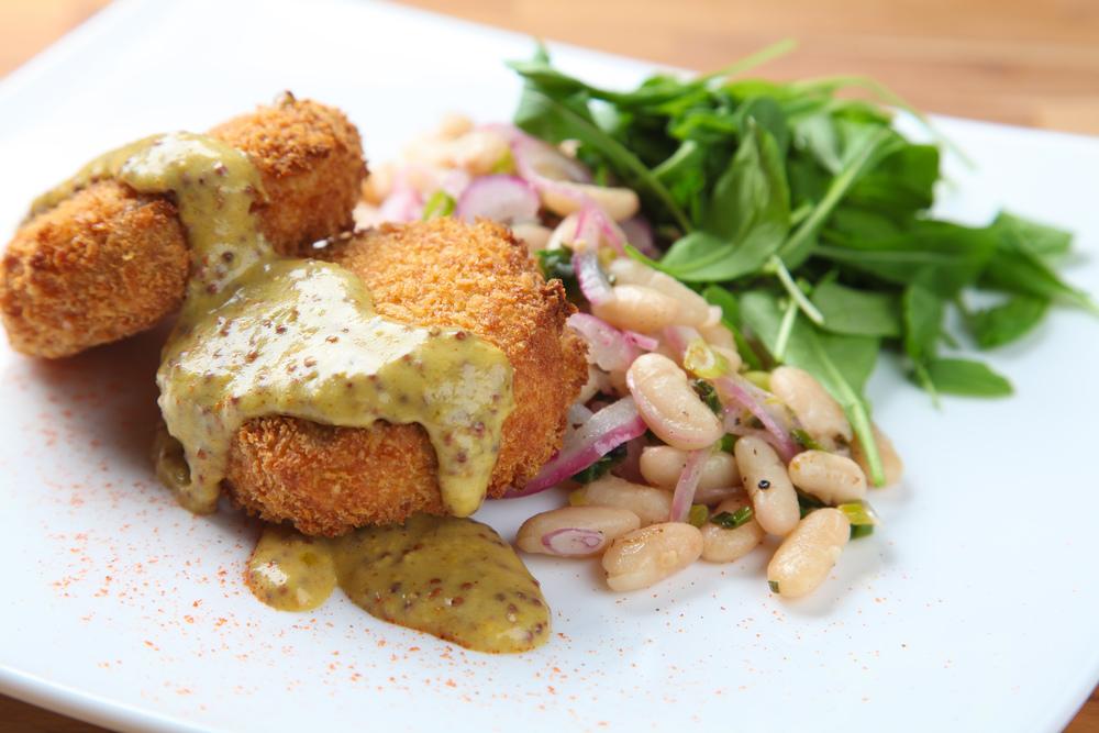 terrine de porco crocante com feijão branco salteado, cebola roxa e molho de mix de mostarda e rôti.