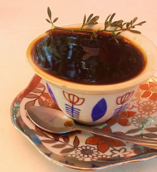 A typical cup of Ethiopian coffee with a sprig of tenadam