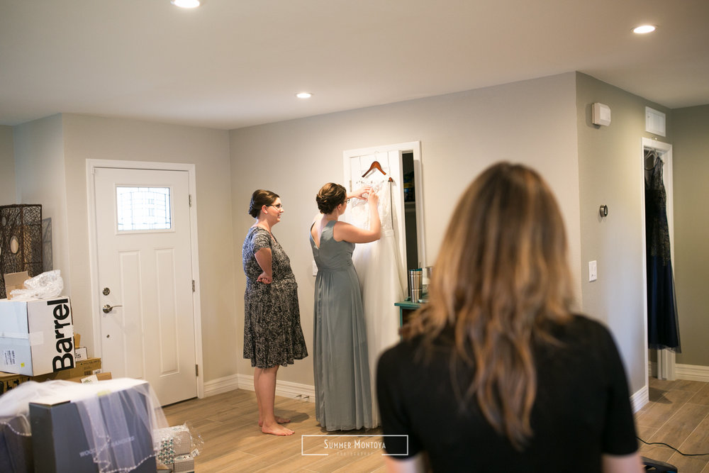 Bride and sister adjusting wedding dress