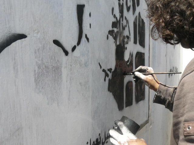 Murad Painting the faces of victims in Hadda, Sana'a. Photo by Najeeb Subay'