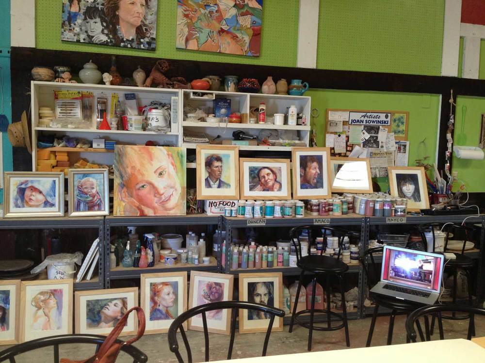 Some of my portrait paintings displayed against Burning House Art Studio interior.