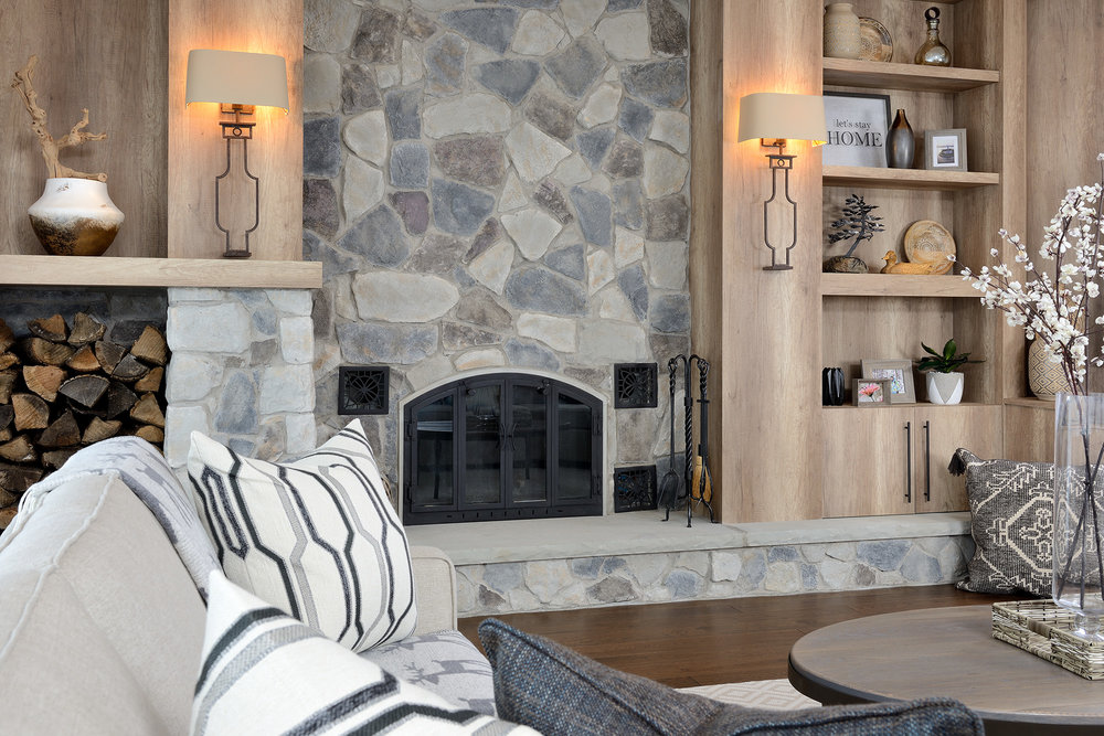 The cultured stone fireplace is accented by italian wood-look laminate which has a texture and the feeling of a rustic interior.