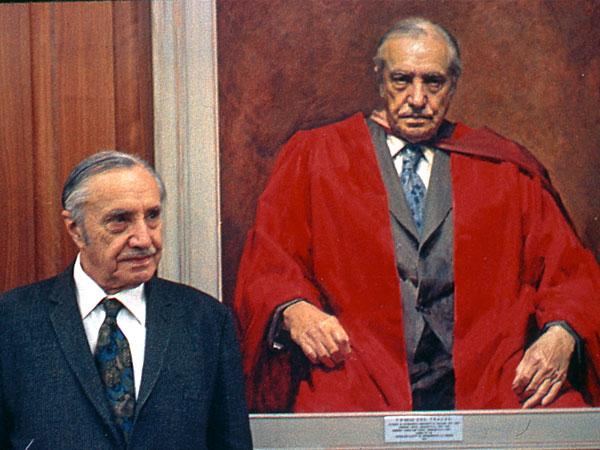Dr P R Begg alongside a portrait of himself.