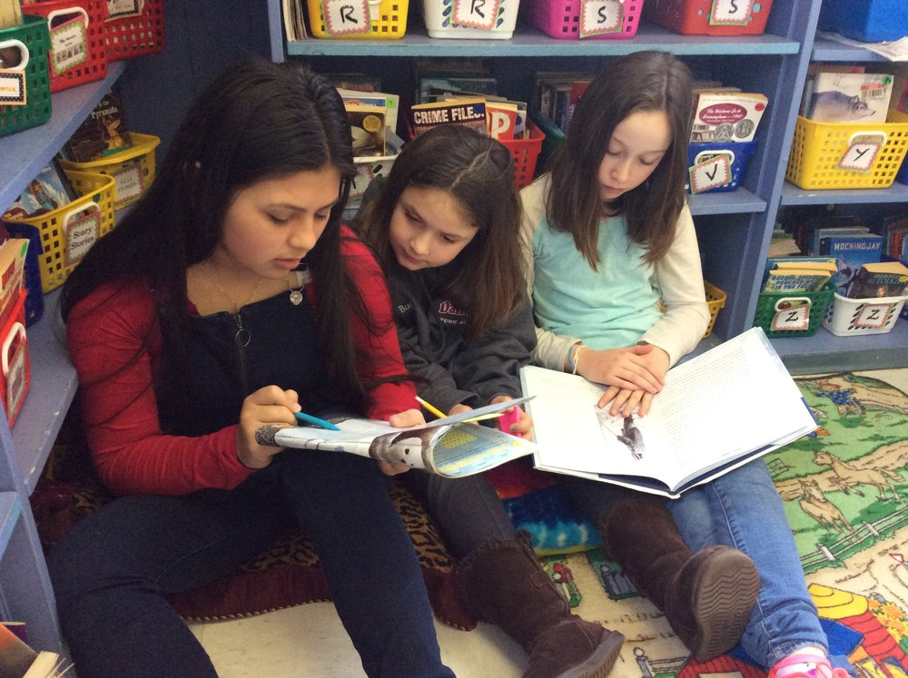Alisson, Lydia, and Caroline research Arctic animal facts.