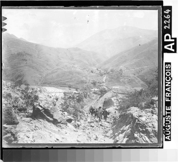 Chemin pierreux en descente, file de porteurs, vallée avec champs en terrasse à gauche, no date, gelatin silver glass plate negative