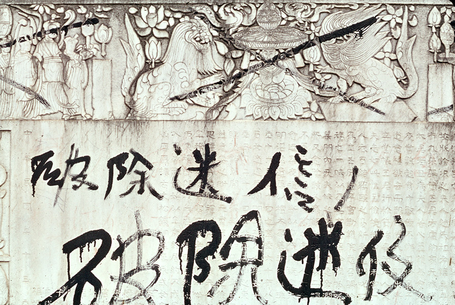 "November 1966. Graffiti written by red guards on a tombstone representing buddhist sculptures. ""Against religious superstitions."" © Solange Brand."