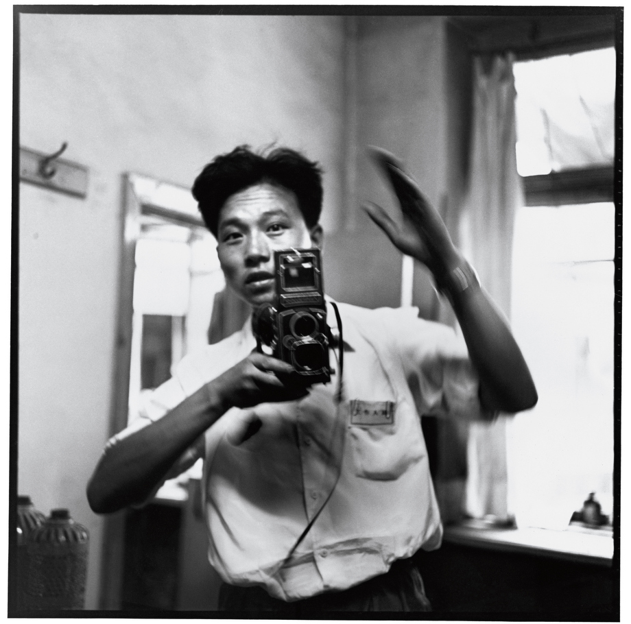 Li Zhensheng in his office holding his Rolleiflex (photographed with another medium-format camera set on a self-timer). 17 July 1967